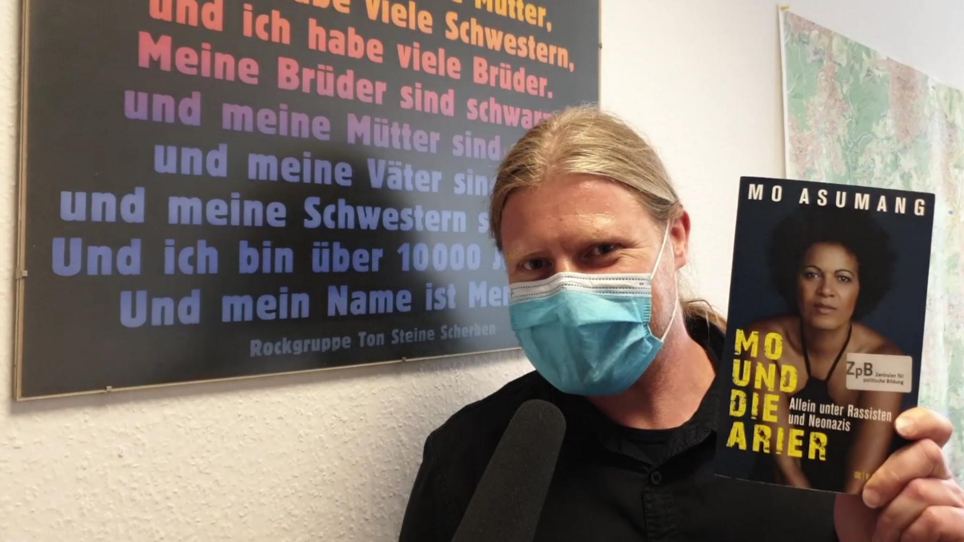 """Christoph Sykulski vom Kommunalen Integrationszentrum (KI) mit dem Buch: """"Mo und die Arier"""" von Mo Asumang."""